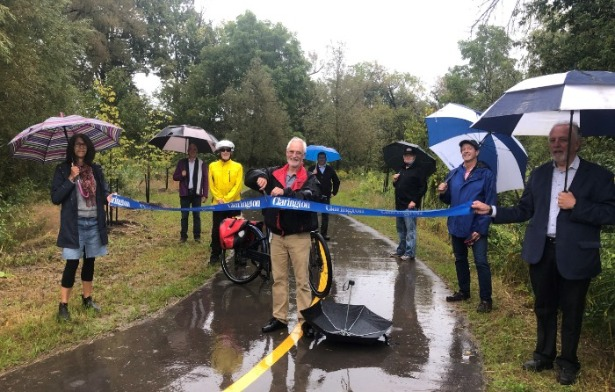 Councillor Hooper and Councillor Zwart hold the ribbon across the trail as Mayor Foster cuts it in the middle at the opening of the Bowmanville Valley Trail extension opening