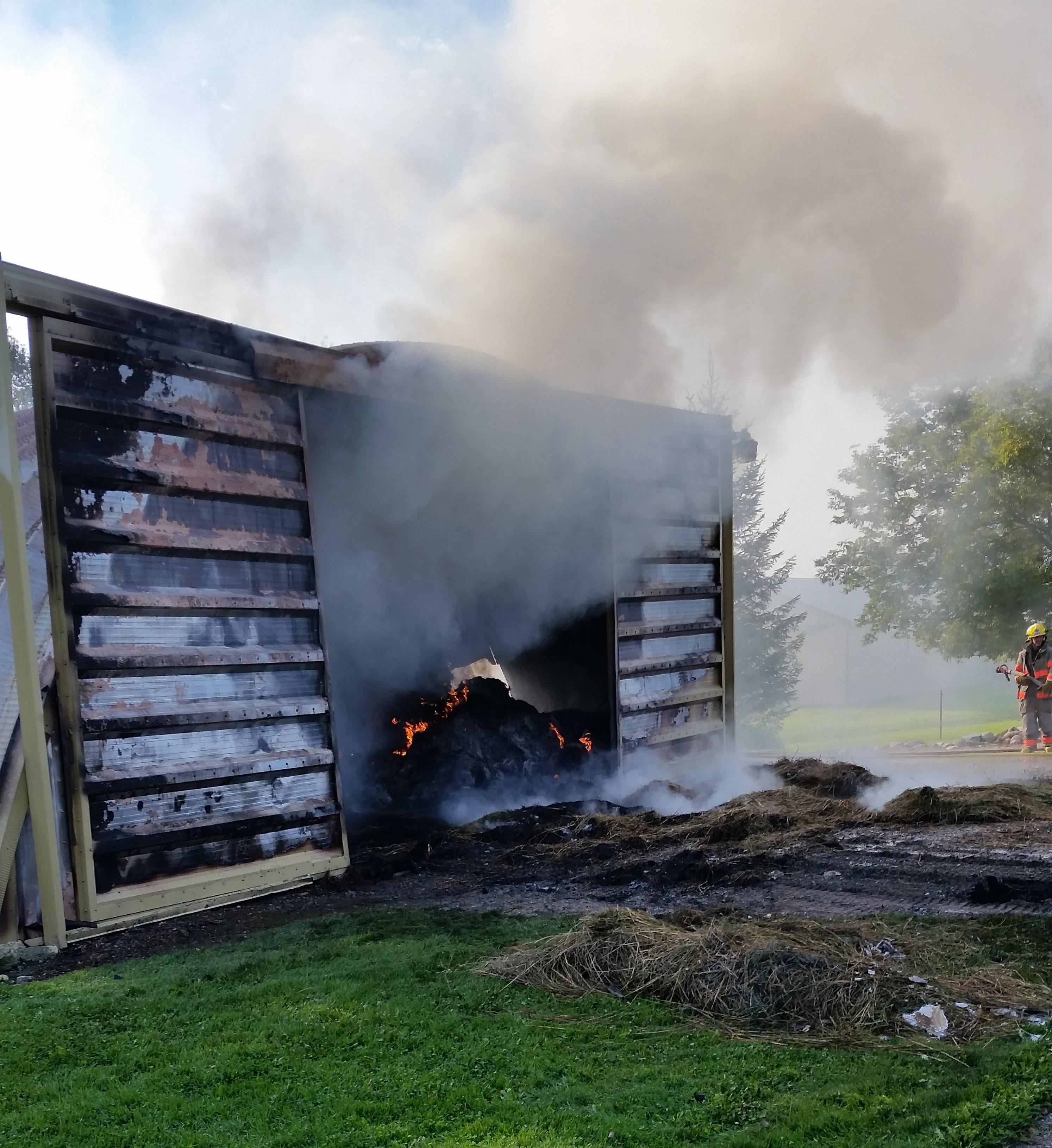 Heavy smoke billows through barn door as hay bales burn