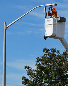 A worker replaces a streetlight bulb